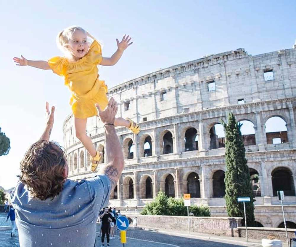 Father throwing girl in the air in Rome Italy