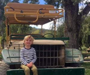 little boy sitting on front of safari jeep