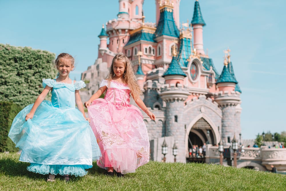 Little cute happy girls in beautiful princess at fairy-tale park
