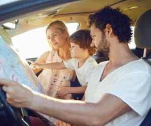 mom, dad and little boy in the car looking at the map. family road trip games