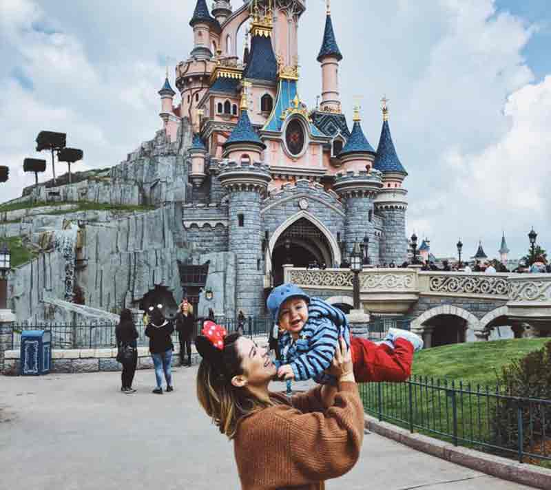 Mother holding a child in front of Disneyland, Paris. 5-day itinerary in Paris with kids