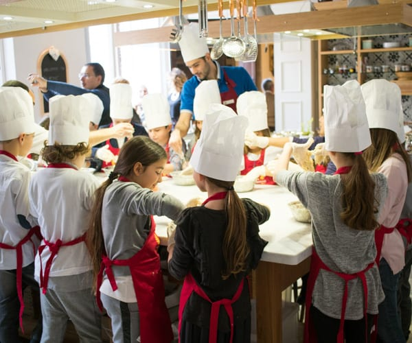 Cooking class in Rome with young children in white chef hats