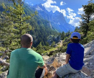 Father and son sit looking out onto the Grand Tetons.
