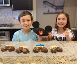 Two kids pose with a Mickey Mouse hat and Mickey Mouse shaped rice cereal treats.