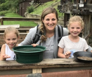 A mom and two young daughters sit smiling as they show off the gold they panned in South Dakota.