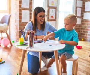 Little boy sitting on a table in a kids club with a nanny. how to find child care on your family vacation.