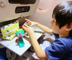 Small boy playing with toys on an airplane.