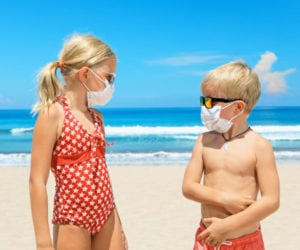 Two kids on the beach wearing a mask and looking at each other