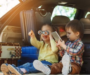 Kids sitting on the back of the car trunk with pad and binocular